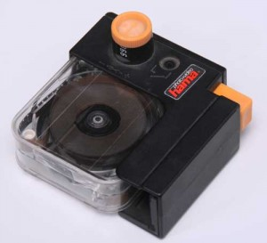 Filmrückwickler (mit eingesetzter Filmkassette aus Plexiglas) von Hama: Nicht so weit verbreitet wie der ewa-Rückwickler, dafür aber mit einem komfortabel ablesbaren Einzelbildzählwerk ausgestattet. In Verbindung mit einem geeigneten Elektro- oder Drahtauslöser ist das Zahlwerk auch für Trickfilm geeignet.